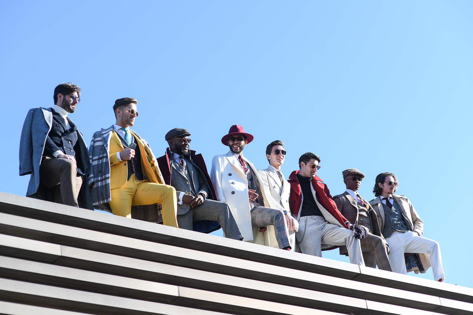 The influencers of Pitti are posing on top of the exhibition spaces looking over the crowd and photographs