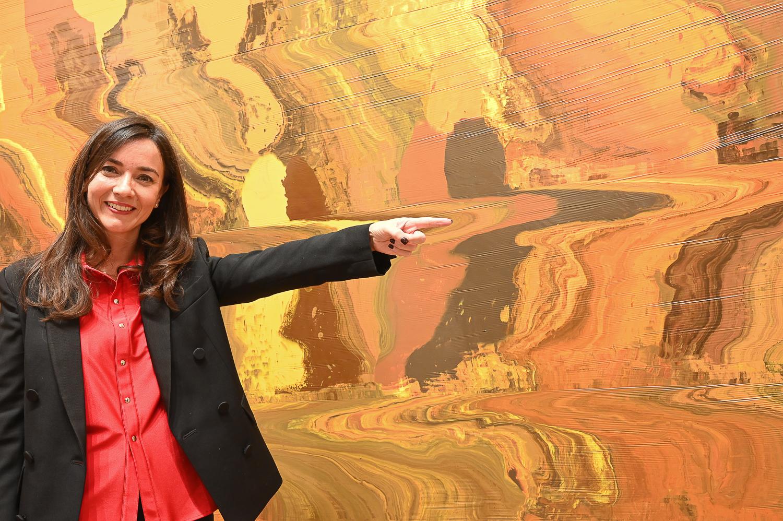 Delphine Souquet in front of Mimetita II 2019 painting of José Yaque