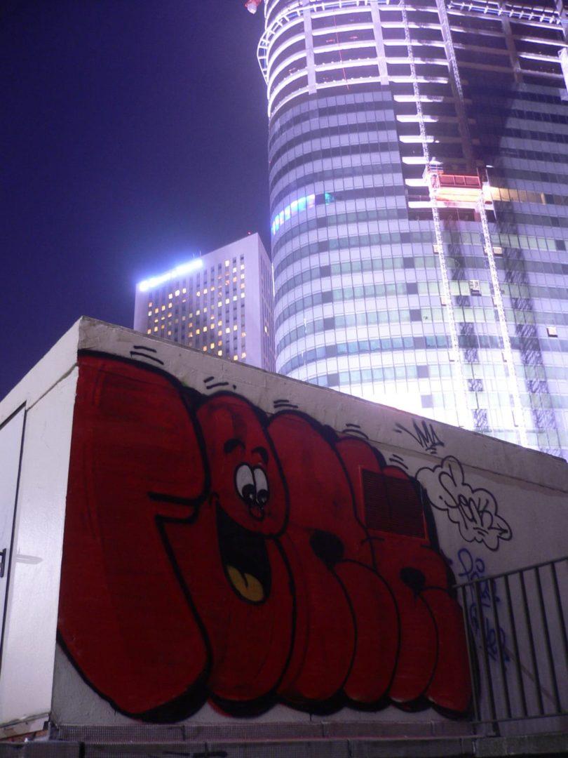photo de nuit d'un Tag de graffiti de FENX dans le quartier de La Defense Paris